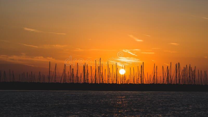 Horisontalfoto av skymning Aftonhimmel har orange färg och få moln Solen är nära horisont Många skepp med konturer av master arkivfoto