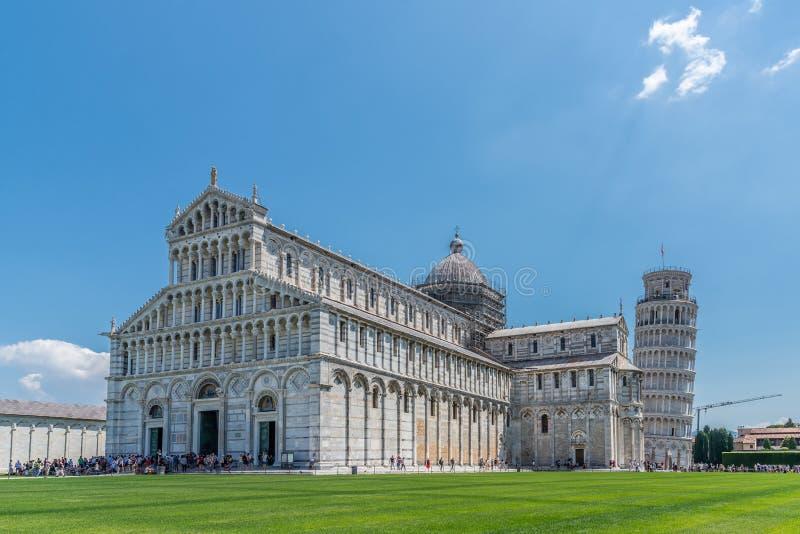 Horisontalfoto med den berömda domkyrkan på piazzadeien Miracoli i den italienska staden Pisa Benägenhettornet är i bakgrund Gräs royaltyfri foto