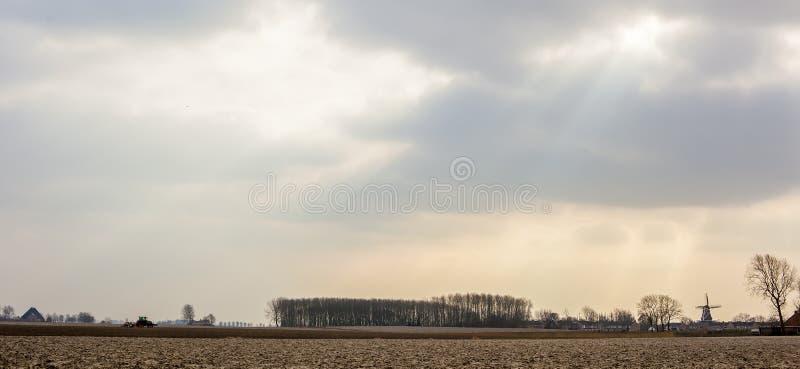 Horisontalpanorama av europeiska åkermarkfält, som traktoren rider på och i avståndet som ses en väderkvarn och, inhyser royaltyfria foton