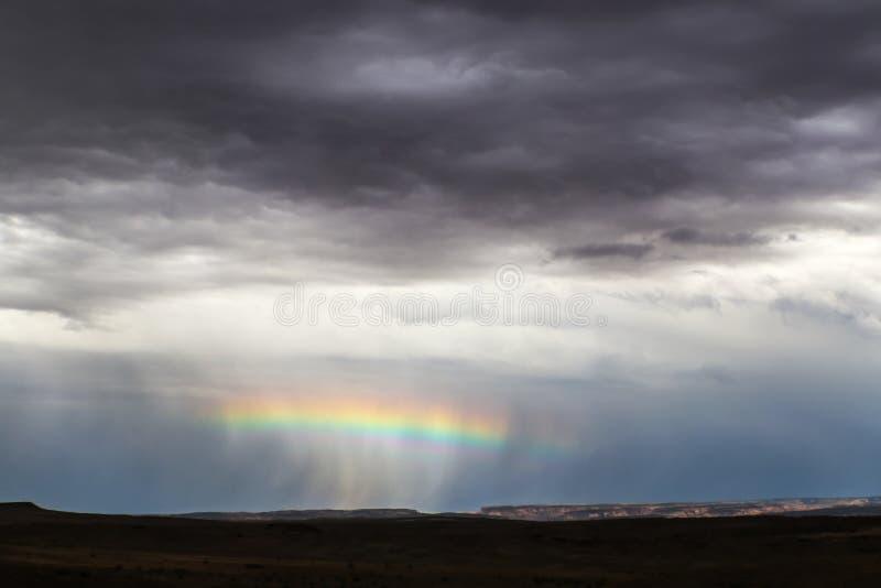 Horisontalregnbåge över mitt av ett regntjut nära horisonten i öken med avlägset klippa- som tänds upp, och förgrundsmörker - arkivbild