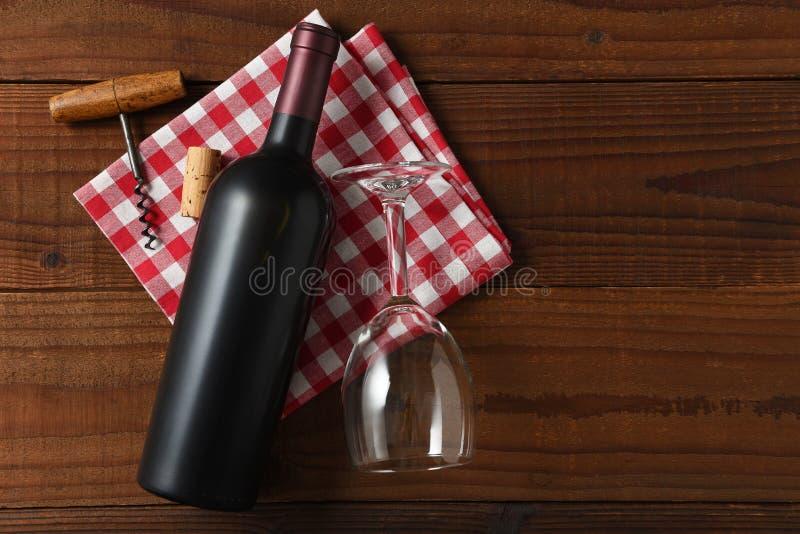 Horisontalsikt för hög vinkel av en rött vinflaska på en röd och vit rutig servett arkivfoton