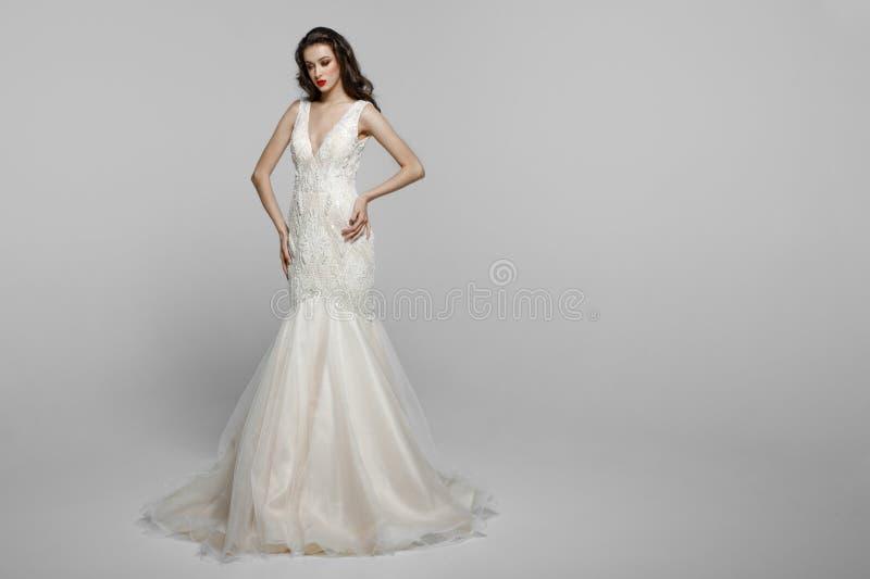 Horisontalsikten av en härlig kvinnlig modell med långt hår, utgör i den wendding klänningen som isoleras på en vit bakgrund royaltyfri foto