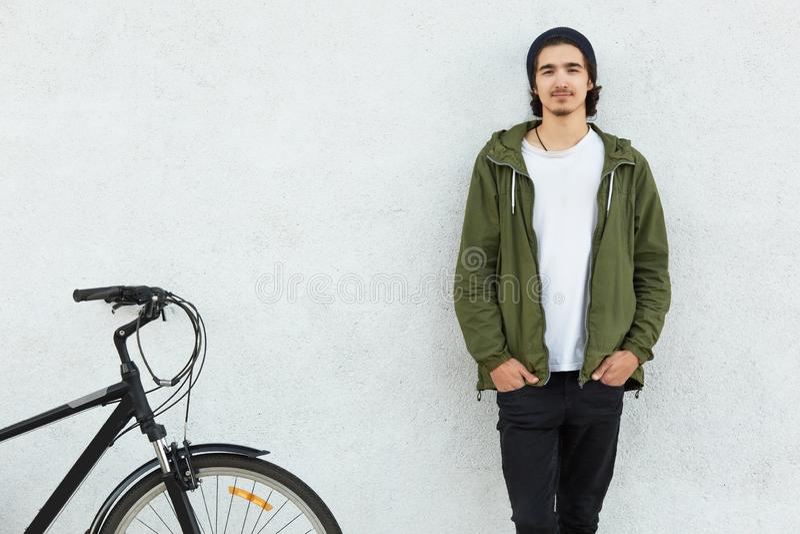 Horisontalsikten av stilfulla manuppehällehänder i fack av svart byxa bär det gröna omslaget, står nära hans cykel, gillar att cy royaltyfria bilder