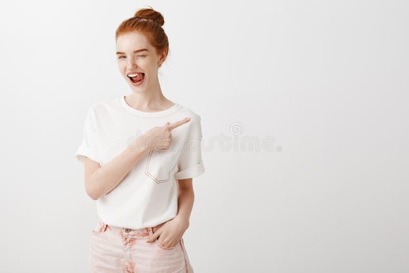 Horisontalskott av den stilfulla bekymmerslösa kvinnliga rödhårig mankvinnan i den vita t-skjortan och moderiktig jeans som ut bl royaltyfria bilder