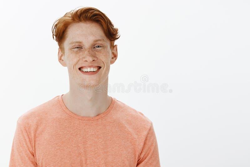 Horisontalskott av den unga mannen för charmig säker rödhårig man med fräknar och ljust leende som joyfully grinar och stirrar på arkivbild