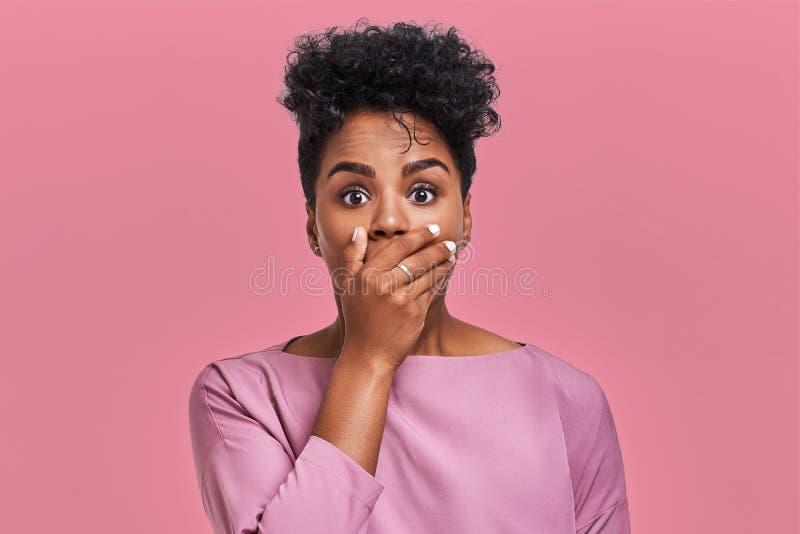 Horisontalskottet av den förvånade afrikansk amerikankvinnan täcker munnen med båda händer, försök att vara mållöst, ser med royaltyfria bilder