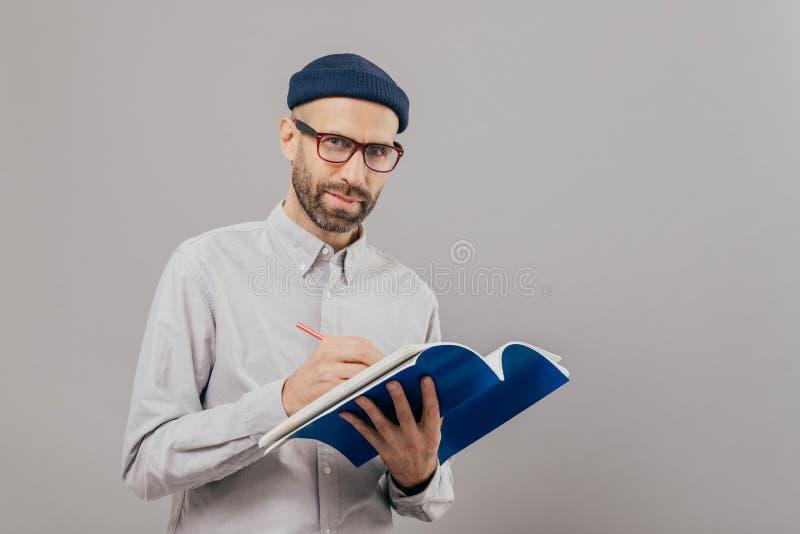 Horisontalskottet av den koncentrerade manliga copywriter skriver idéer för ny strategi, rymmer den blåa notepaden, bär anblickar fotografering för bildbyråer
