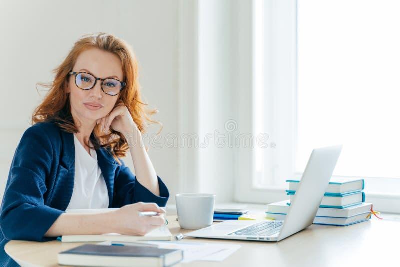 Horisontalskottet av den kvinnliga företagsägaren för den säkra lyckade rödhåriga mannen sitter på kabinettet, arbeten på bärbar  arkivbilder