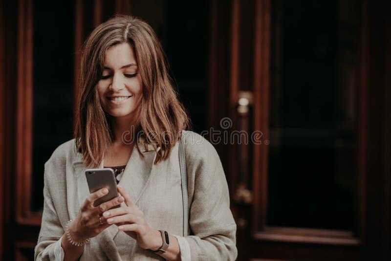 Horisontalskottet av den kvinnliga modellen för den nätta gulliga brunetten delar multimediamappar via mobiltelefonen, iklädd ele royaltyfri fotografi
