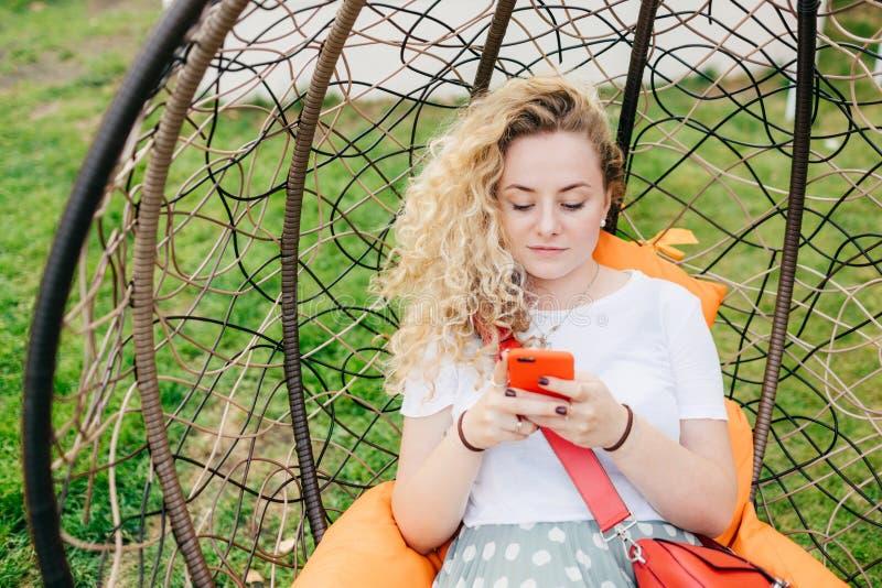 Horisontalskottet av den nätta unga kvinnlign vilar i hängande stol i trädgård, bruk ilar telefonen och att vara alltid in handla royaltyfria foton