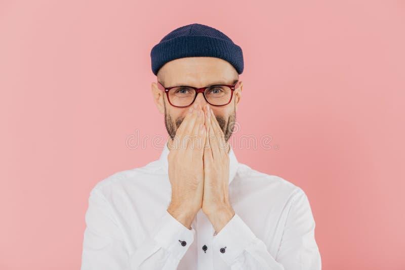 Horisontalskottet av den positiva glade mannen uttrycker positiva sinnesrörelser, täcker munnen med båda händer, fniss tyst, bär  arkivfoto