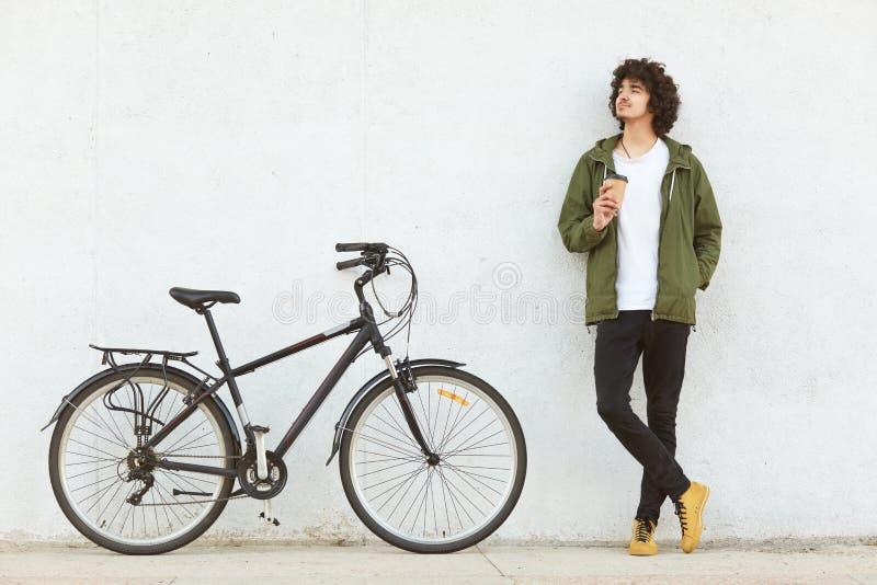 Horisontalskottet av manliga cyklisttagande bryter under cykelritten, takeaway kaffe för drinkar, iklädd trendig kläder, tänker o royaltyfria bilder