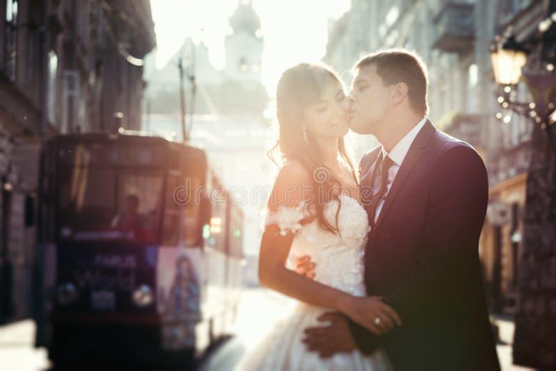 Horisontalstående av den stiliga brudgummen som kysser den härliga le bruden under solnedgången Stadgataläge royaltyfri fotografi
