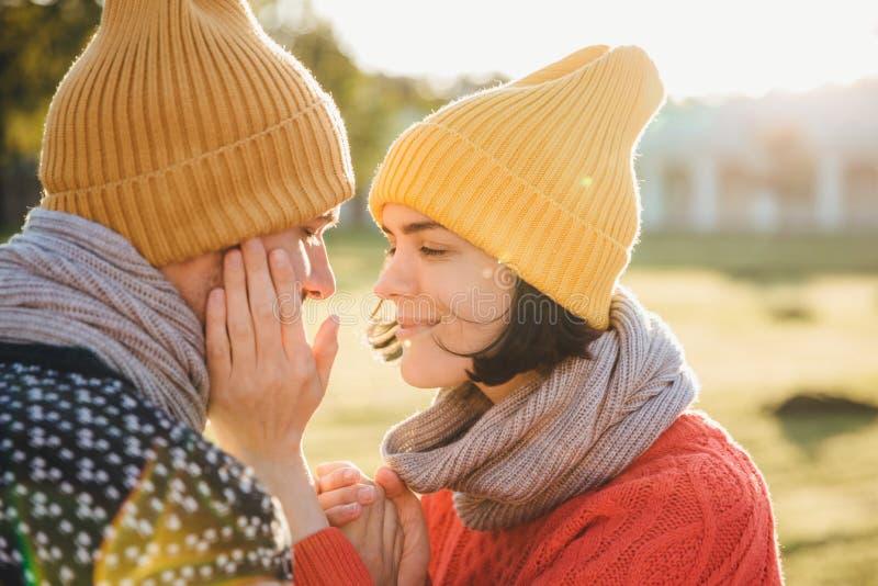 Horisontalståenden av brunettkvinnlign i den varma hatten, halsduken och tröjan, uppehällehänder på pojkvän` s är fräck mot, har  royaltyfri bild