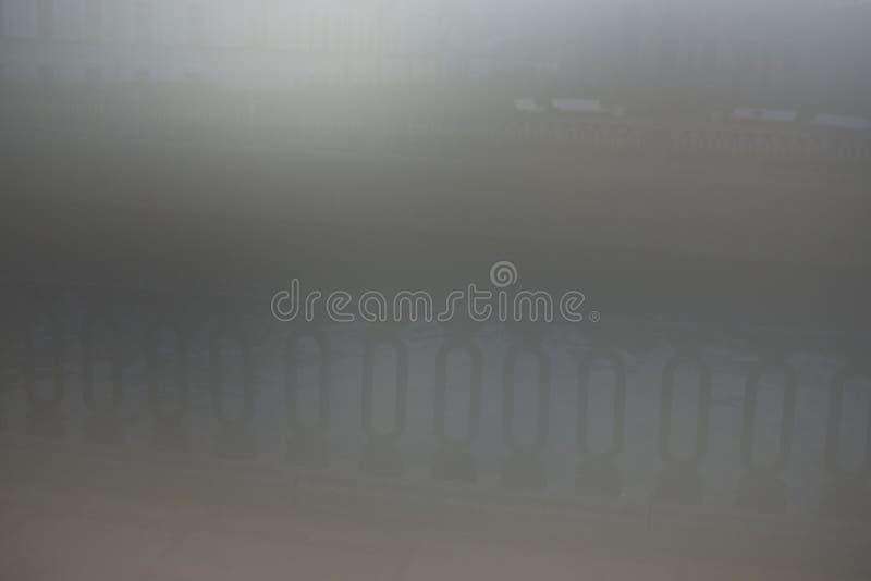 Horisontalstadsmetallstaket i den gråa dimman royaltyfri fotografi
