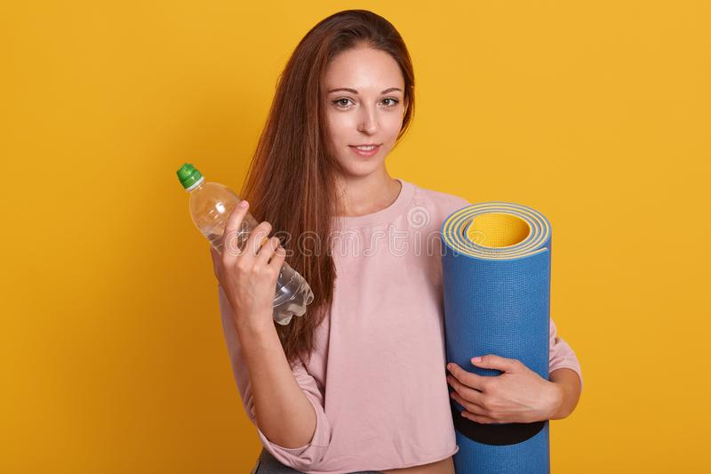 Horisontell bild av en vacker, liten, sportig kvinna med yoga mat och flaska vatten isolerat över gul bakgrund, mörkhårig dam arkivbild