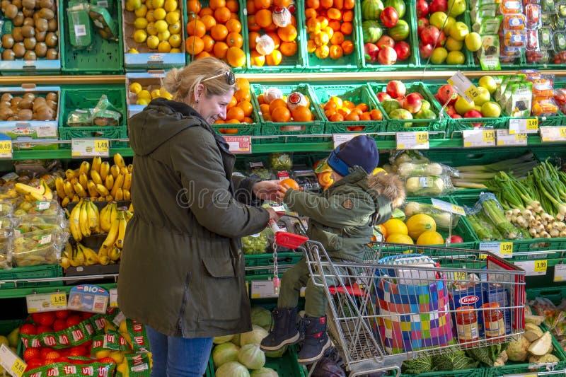 Horitschon, Áustria - 02 08 2018: mulher com seus vegetais e frutos da compra do filho no supermercado fotografia de stock royalty free