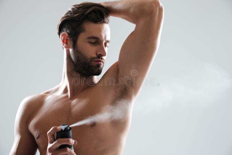 Horizntal bild av den unga mannen som använder deodoranten arkivbilder