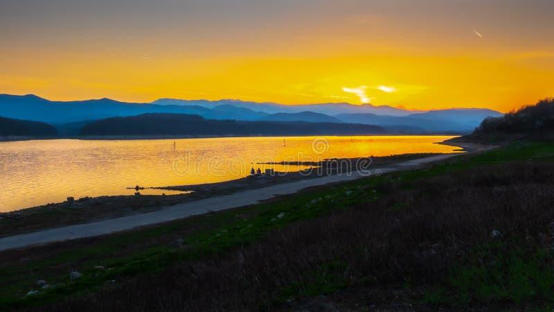 Horizon d'or de coucher du soleil par un lac photo libre de droits