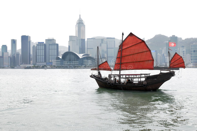 Horizon de Hong Kong avec le vieux bateau traditionnel d'ordure, voiles rouges images libres de droits