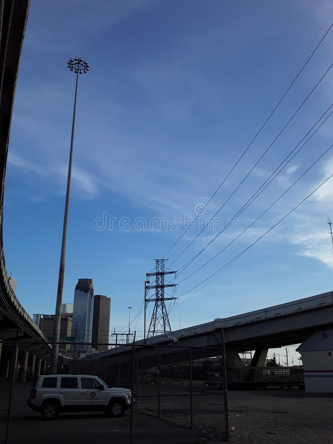Horizon de Houston Texas avec des lignes à haute tension, des gratte-ciel, des autoroutes, des nuages effilés et une voiture blan photographie stock