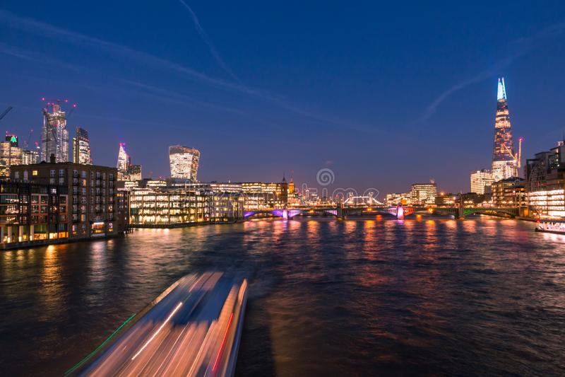 Horizon de Londres avec le cardon, les ponts de Londres et les bateaux de rivière croisant la Tamise la nuit image stock