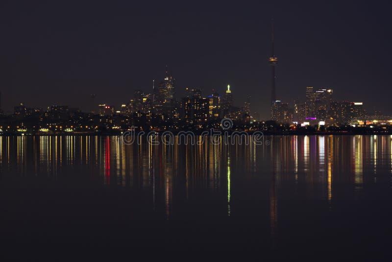 Horizon de ville de Toronto la nuit, ciel fonc? clair, r?flexion de la lumi?re color?e dans la surface calme de l'eau du lac Onta image stock