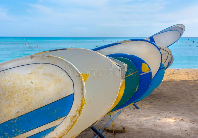 Surf Boards stacked in line on Hawaiian Beach. Horizon filled with swimmers in clear blue waters of Hawaii.  Surf boards well worn and banged up await the next stock photo