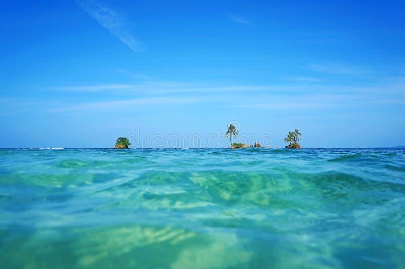 Horizon over water with islets and coconut tree. Horizon over water with small islets and coconut tree, Caribbean sea, Zapatillas Keys, Bocas del Toro, Panama royalty free stock images