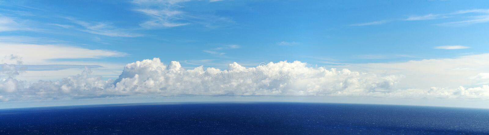 Horizon to heaven. The dark blue waters of the of the ocean around the island of Fogo, Cabo Verde, gives away to a clear horizon line with blue skies and puffy stock photography