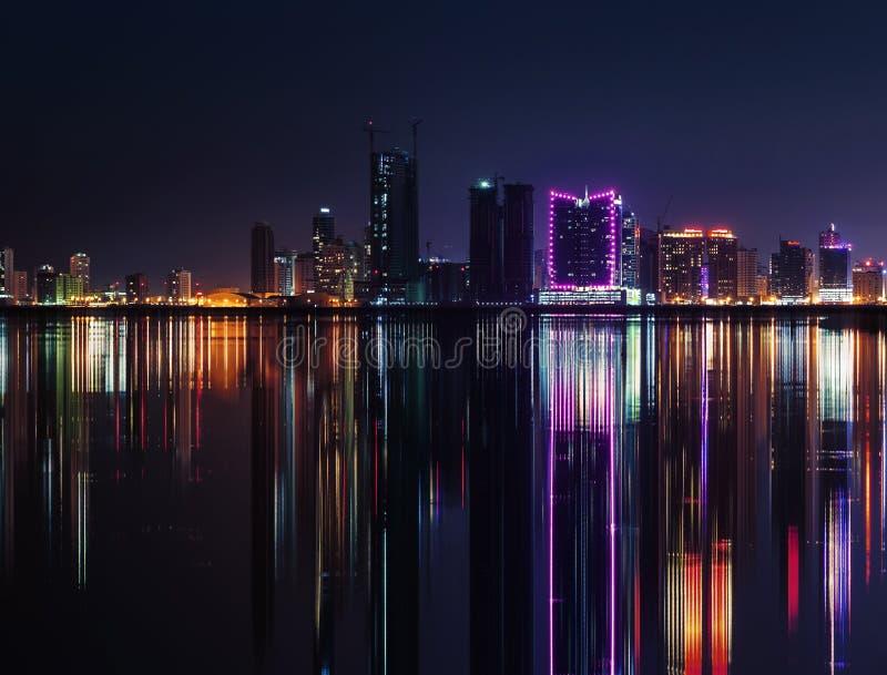 Horizon van de nacht de moderne stad met neonlichten en bezinningen stock afbeeldingen