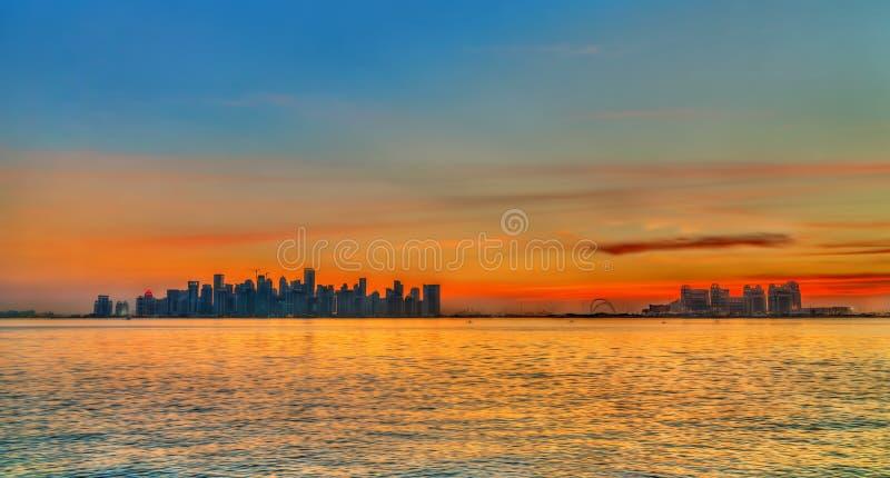 Horizon van Doha bij zonsondergang De hoofdstad van Qatar royalty-vrije stock afbeelding