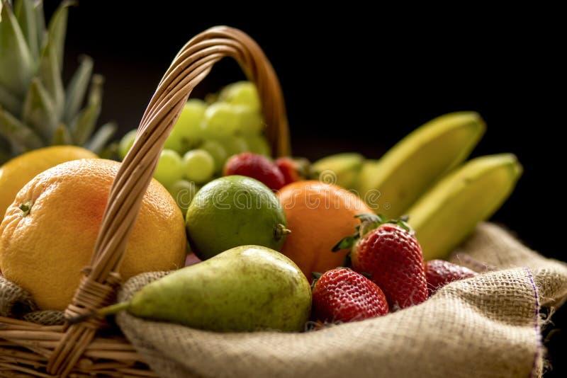 Horizontaal Close-updetail op een mandhoogtepunt van fruit op een donkere achtergrond stock foto