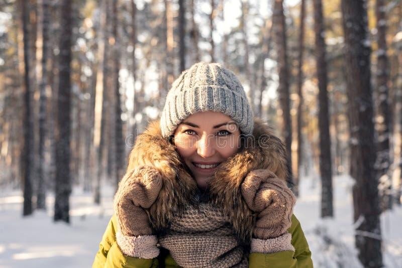 Horizontaal de winterportret van een jonge vrouw op een naald bosachtergrond op een Zonnige dag Meisje in een jasje met bont, geb stock foto's