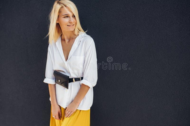 Horizontaal die portret van vrij jong blondewijfje wordt geschoten die en aan één kant tegen grijze muur op de straat glimlachen  royalty-vrije stock afbeelding