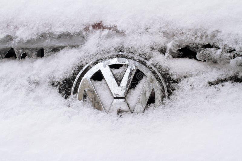 Horizontaal die vooraanzicht van Volkswagen-embleem in sneeuw wordt behandeld stock foto's