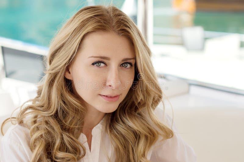 Horizontaal portret van een jonge blonde vrouw met lang krullend haar stock fotografie