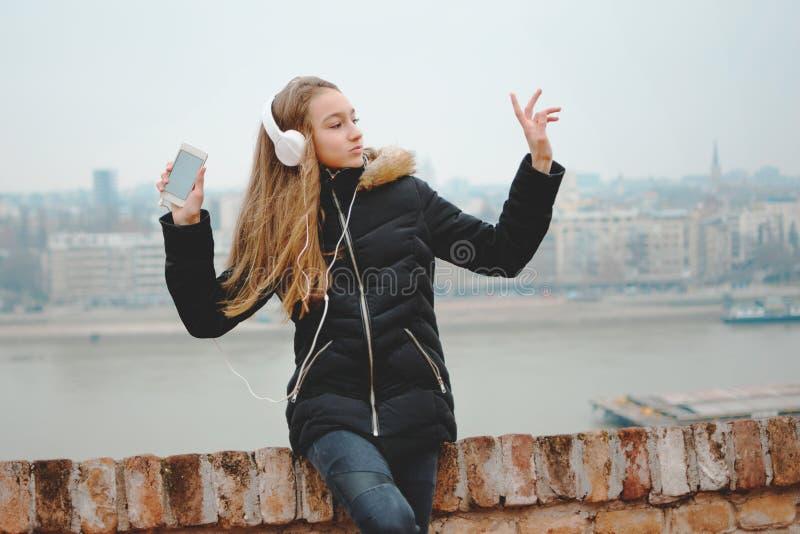 Horizontaal portret van een status wijd glimlachend en dansend jong meisje die een smartphone houden en aan muziek luisteren royalty-vrije stock foto's
