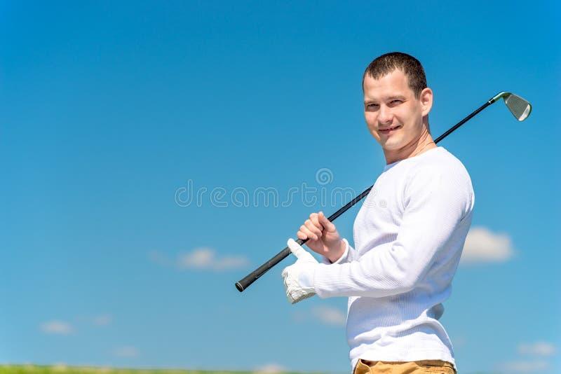 Horizontaal portret van een succesvolle golfspeler met een golfclub stock afbeelding