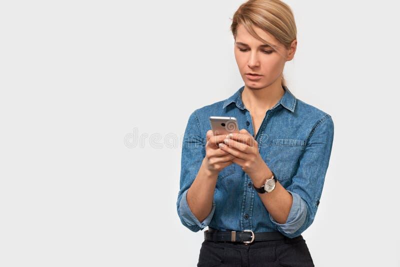 Horizontaal portret van ernstige blondevrouw, texting bericht op smartphone, die denimoverhemd het stellen op witte studioachterg stock foto