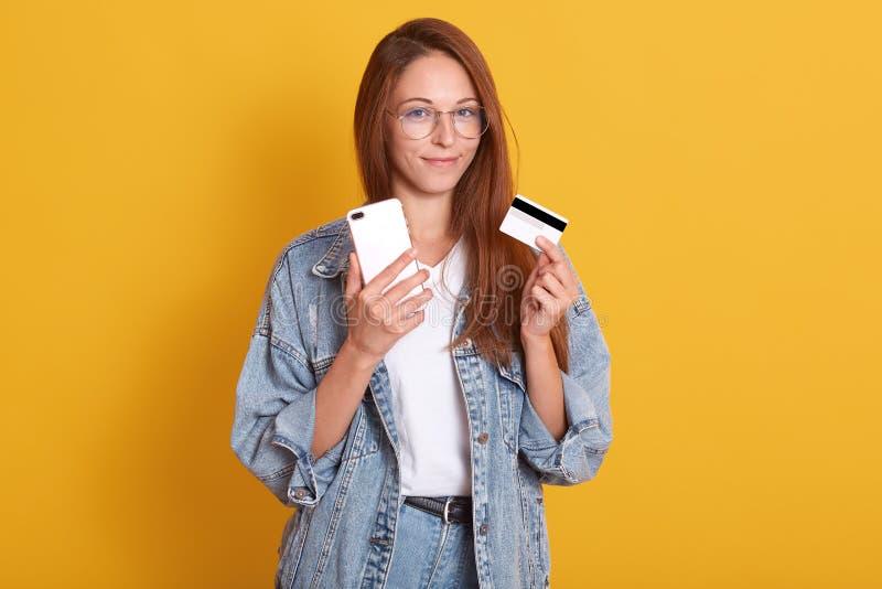 Horizontaal schot van aanbiddelijke glimlachende vrouw die toevallige uitrusting over gele achtergrond wering, die gadget en cred royalty-vrije stock foto