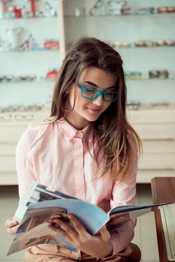 Horizontaal schot van knappe Kaukasische vrouwelijke klantenzitting in in voorgeschreven glazen, lezingstijdschrift en stock afbeeldingen