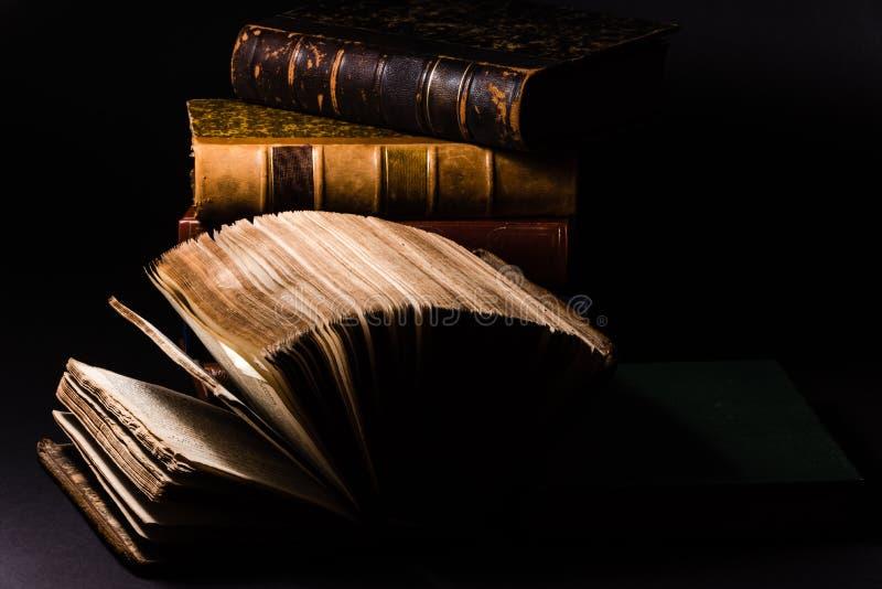 Horizontaal snak schot van een oud boek met zijn die bladen met een zwarte achtergrond worden opgesteld royalty-vrije stock foto