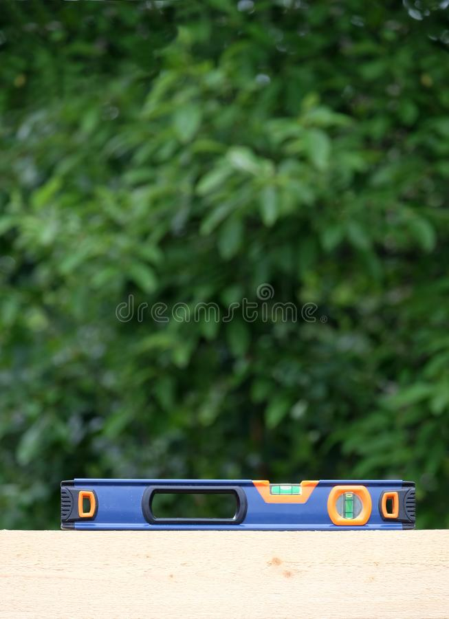 Horizontal bubble level sits on a wooden beam, shows the accuracy of the installation before blur green plant background. The building horizontal bubble level stock image
