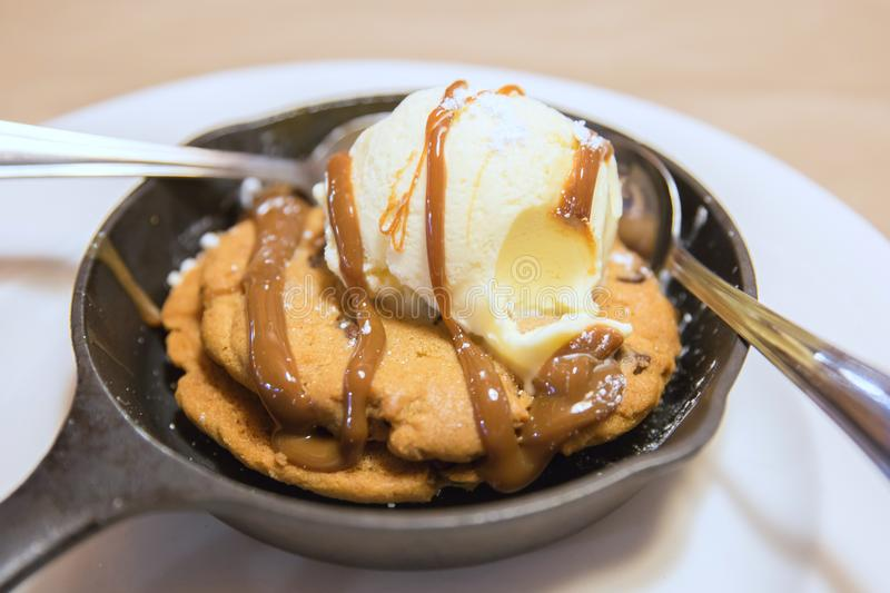 Cookies topped with ice cream and caramel sauce in pan royalty free stock photo