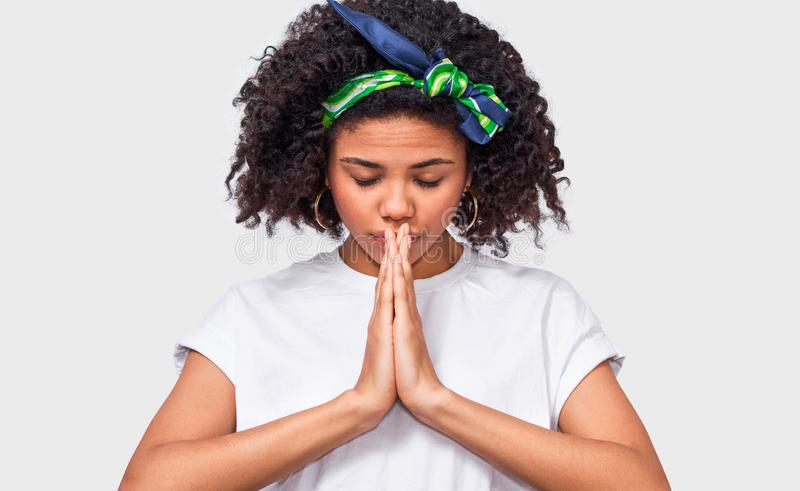 Horizontal close up image of young Afro woman keep hands in praying gesture. stock photography