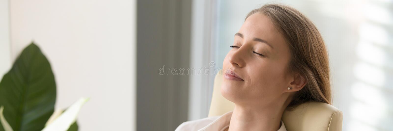 Horizontal image young woman closing eyes resting sitting on chair. Horizontal close up photo businesswoman worker rest leaning on chair at workplace closed eyes royalty free stock photography