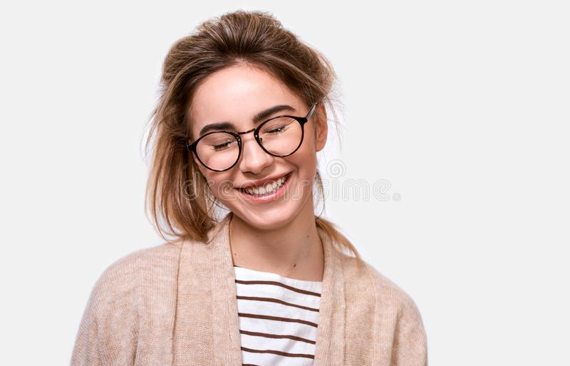 Horizontal close up portrait of dreamful positive female in casual outfit and eyewear, smiling with closed eyes royalty free stock photos