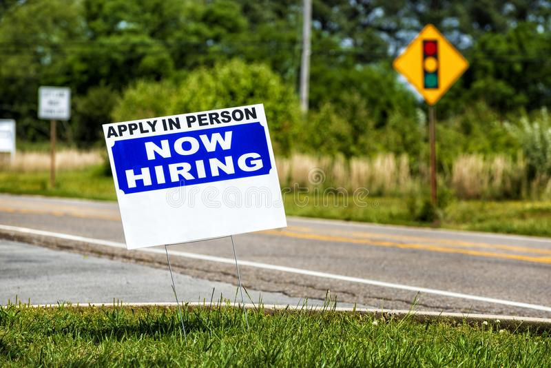 Hiring Sign With Copy Space. Horizontal close-up shot of a Apply In Person, Now Hiring sign with copy space. The background is out of focus royalty free stock photos