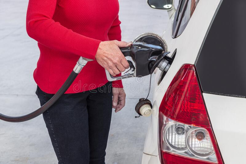 Woman In Red Pumping Gasoline stock photos